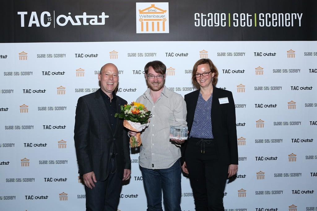 Fabian Iberl von den Münchner Kammerspielen, Gewinner des Weltenbauer Awards 2015, umringt von Arved Hammerstädt, Mitglied des Vorstands der DTHG, und Juliane Trempler, Projektleiterin der StageSetScenery.