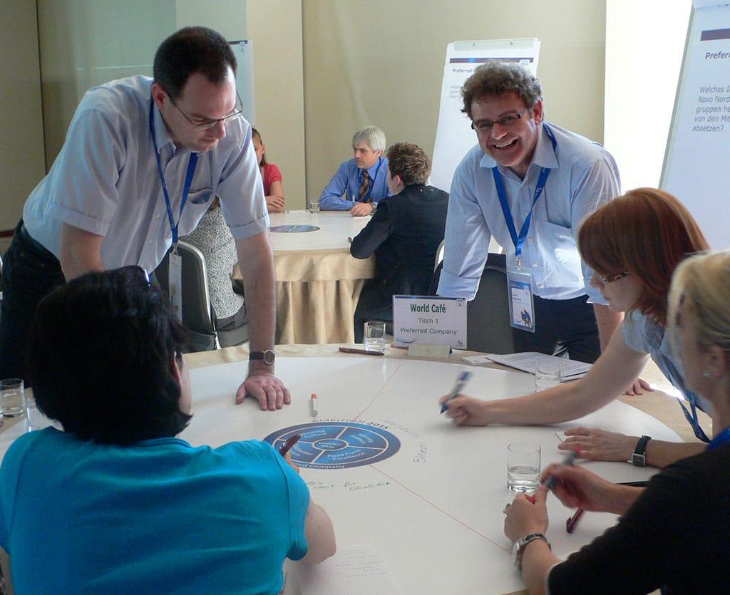 Ein bewährtes Instrument der Großgruppenmoderation ist das World-Café, bei dem sich die Teilnehmer unter Anleitung von Moderatoren an runden Tischen einfinden.