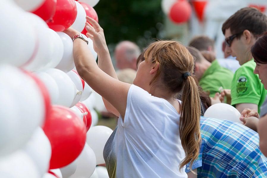 Frau vor zahlreichen Luftballons