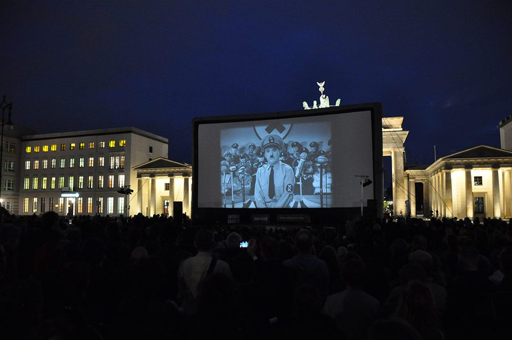 """Charlie Chaplin als """"Der große Diktator"""" vor dem Brandenburger Tor"""