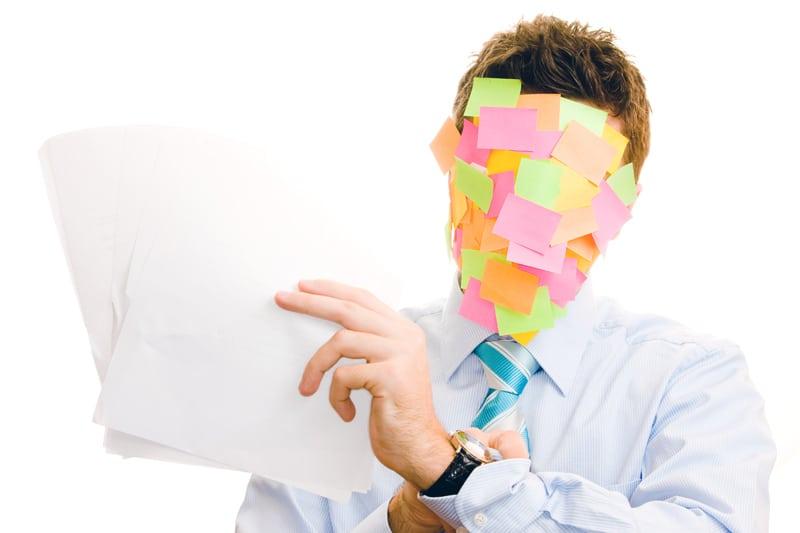 Beschäftigter Arbeitnehmer mit Post-Its im Gesicht