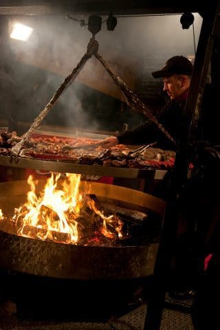 Mann grillt über offenem Feuer