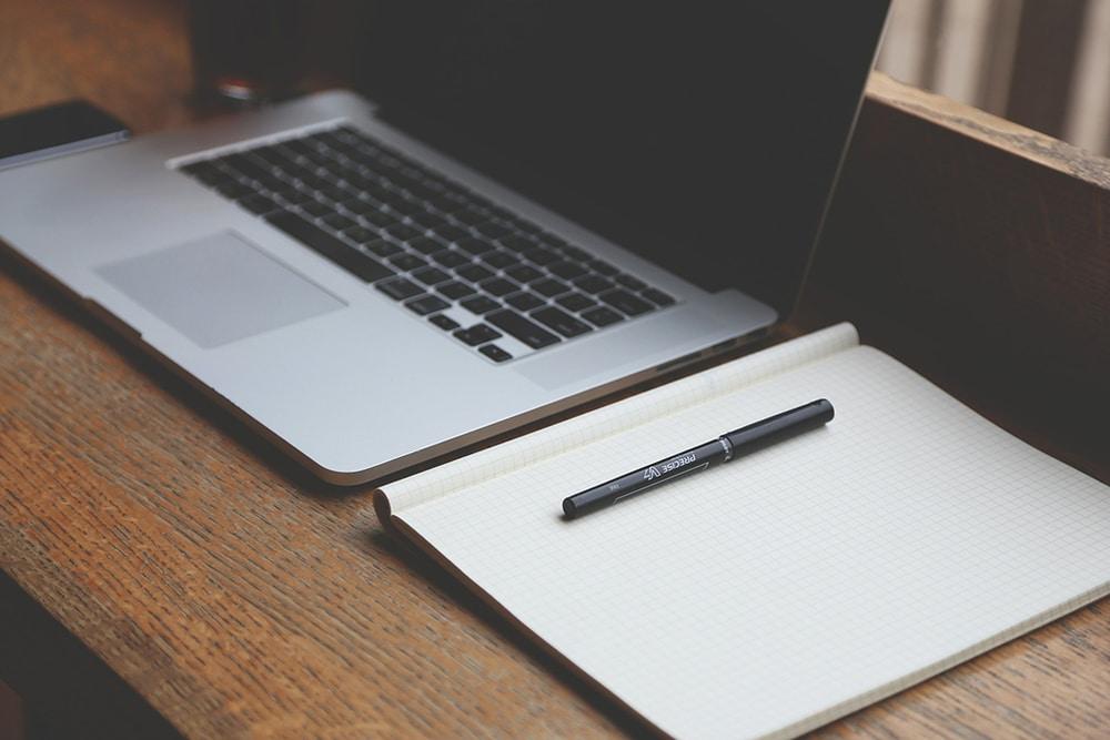 Arbeitsplatz mit Laptop und Notizblatt