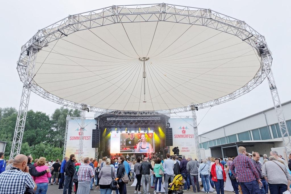 Unmittelbar vor der Hauptbühne beim Windmöller&Hölscher-Sommerfest 2017 war als Regen- und Sonnenschutz ein Skyliner Überdachungssystem mit 22 Metern Durchmesser errichtet worden.