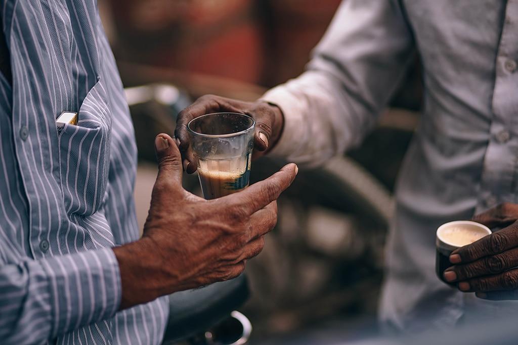 Gastfreundschaft: Ein Mann reicht einem anderen einen Kaffee