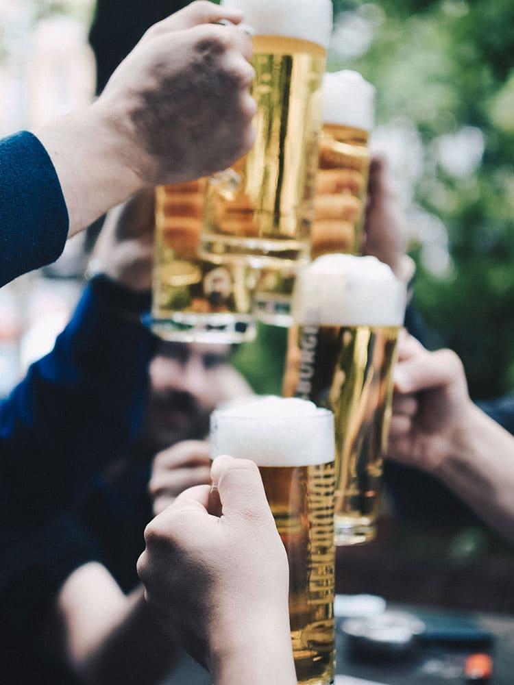 Menschen stoßen mit vollen Biergläsern an