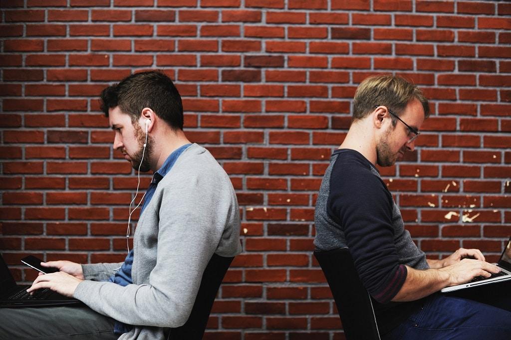 Zwei Menschen sitzen mit Rücken zueinander am Laptop