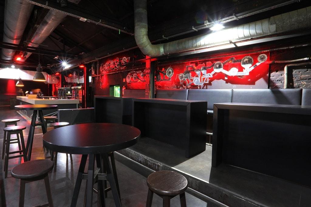 Bristol-Tische in dunkler Optik verstärken den Industrie-Charme der Location.