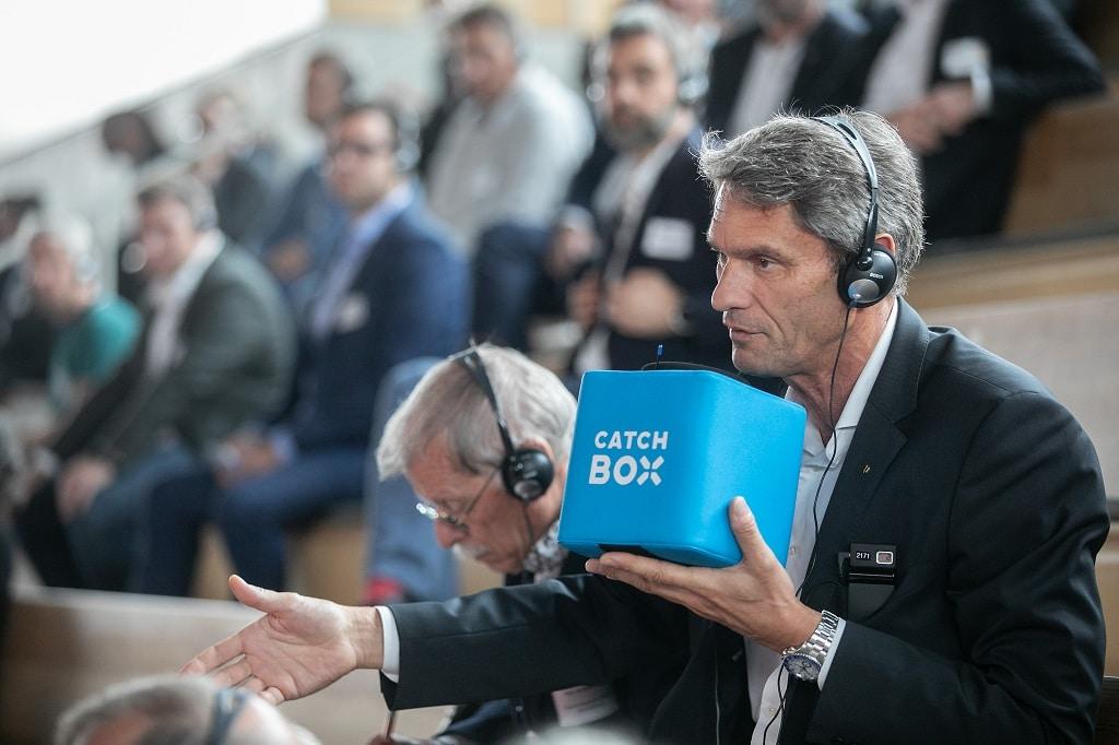 """Ein Gast spricht in die """"Catchbox"""", die für Fragen ins Publikum geworfen wird und mit Mikrofon und Funksender ausgestattet ist."""