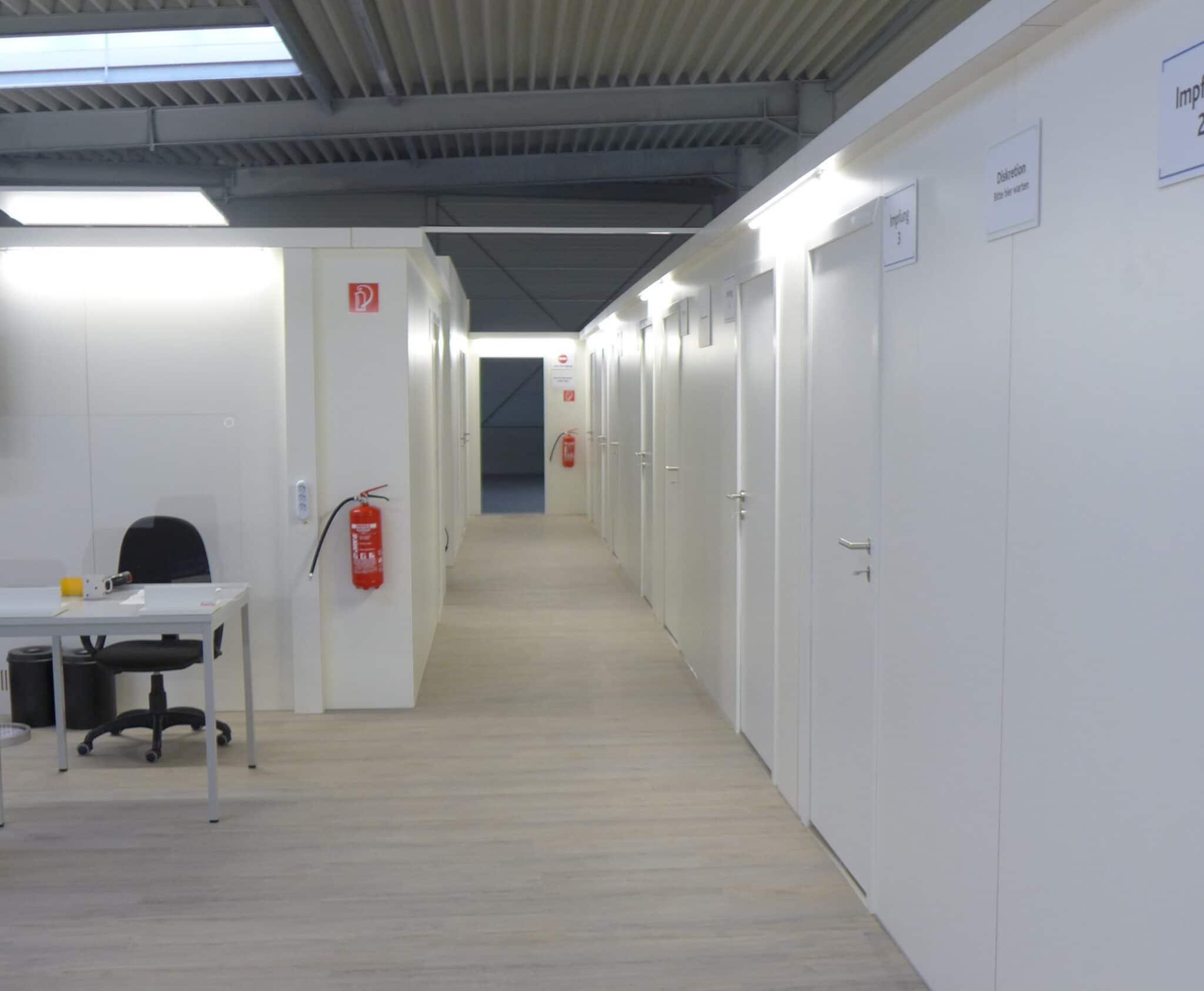Impfzentrum Alzey: Isinger + Merz verbaute in der Fahrzeughalle des DRK ca. 670 m² Laminat und 250 m Trennwandmodule.